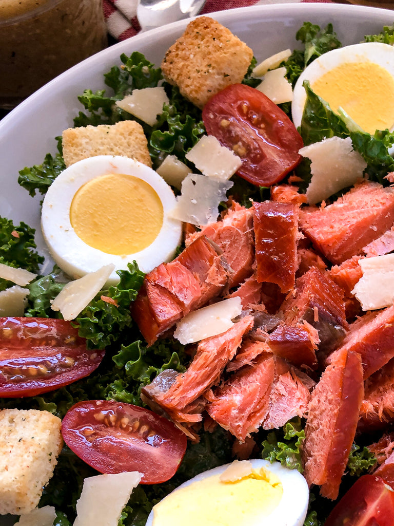 Close up of smoked salmon on a bed of greens with hardboiled eggs and tomatoes.