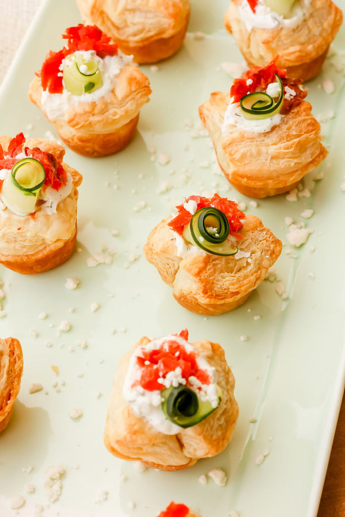 Smoked Salmon Tzatziki Puff ~ The Classic and iconic salmon puff has been given a Greek-inspired makeover with smoked salmon, tzatziki sauce, crumbled feta and a fresh cucumber curl.