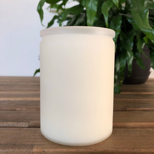 white eco candle on table top, side view