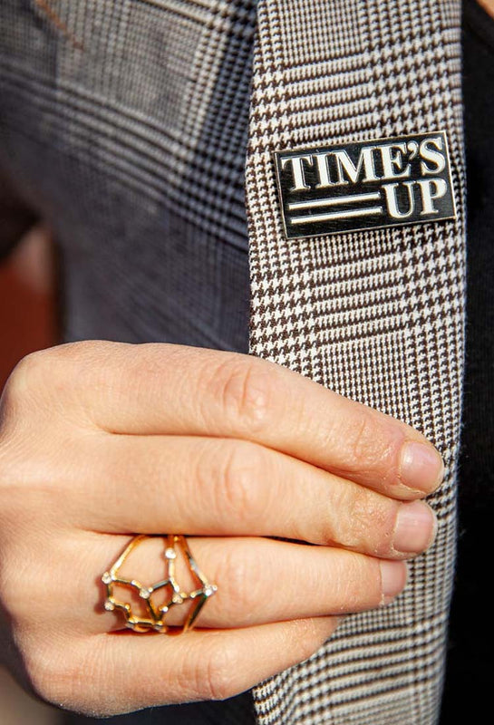 a TIME'S UP pin displayed on a woman's blazer
