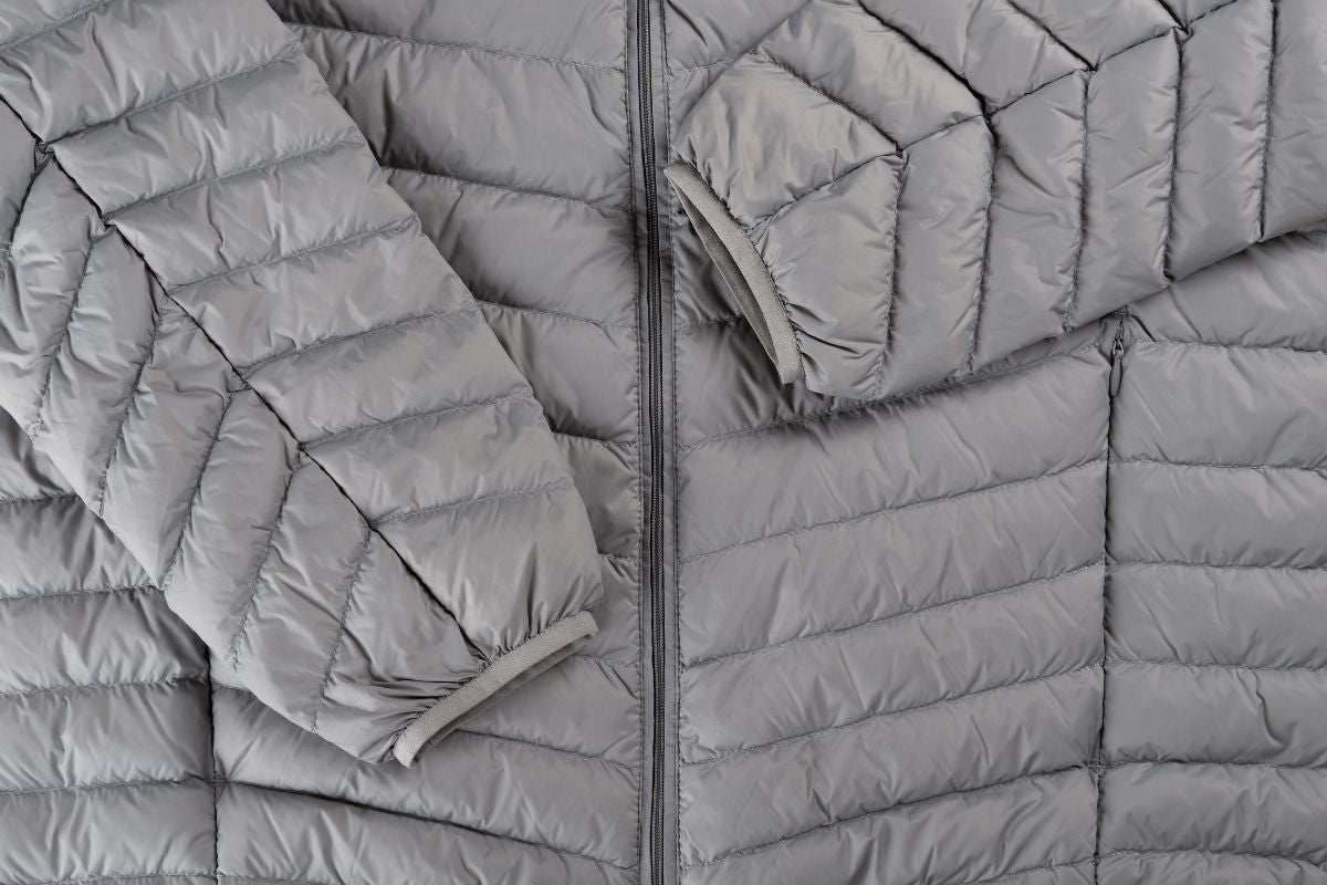 grey duck down jacket laid flat with arms folded over