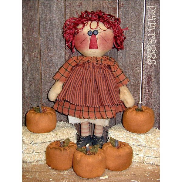fabric raggedy Ann surrounded by tiny pumpkins