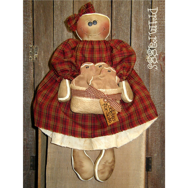 Gingerbread doll in dress holding a bowl of cookies