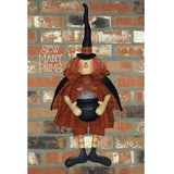 fabric witch doll holding cauldron