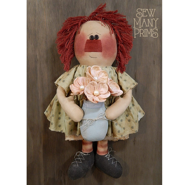 Primitive rag doll holding a fabric mason jar with flowers