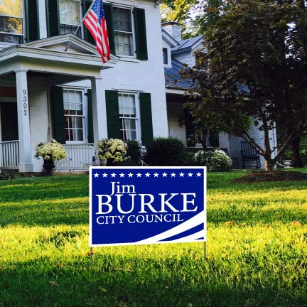 A custom campaign yard sign in the front yard of a house