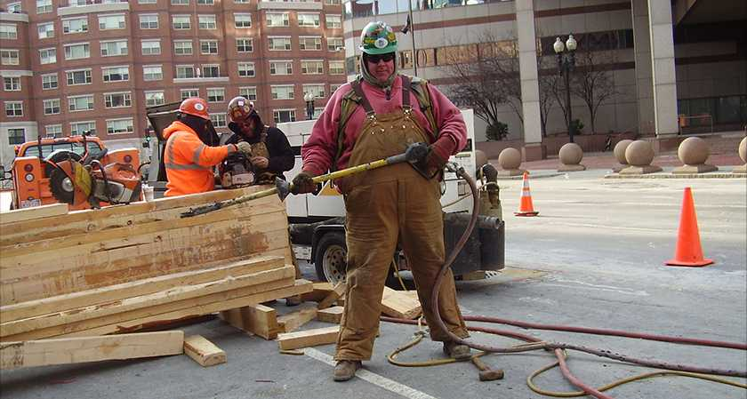 A utility worker posing with the AirSpade 3000 series on a job site in downtown Boston.  Photo credit (if any): John Doe