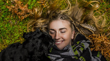 dog cuddling with human on grass