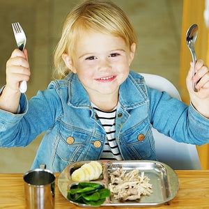 toddler girls is eating with stainless steel flatware and stainless steel dinnerware