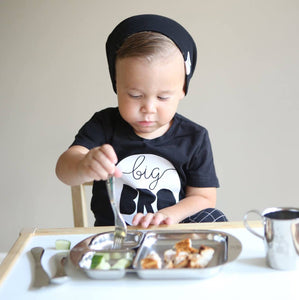 toddler boy eats with stainless steel toddler utensils on a stainless steel divided plate with toddler cup on the side