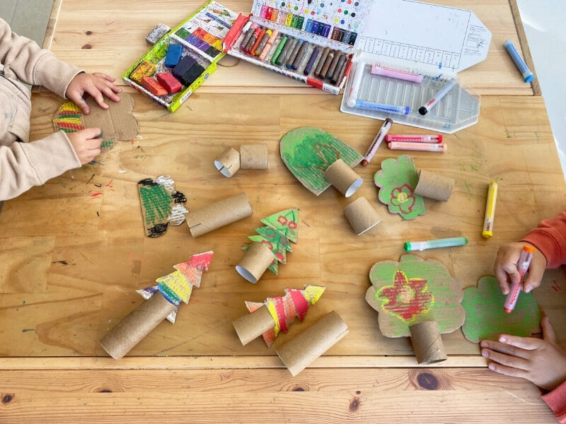 Attach the tree shapes to the cardboard rolls.