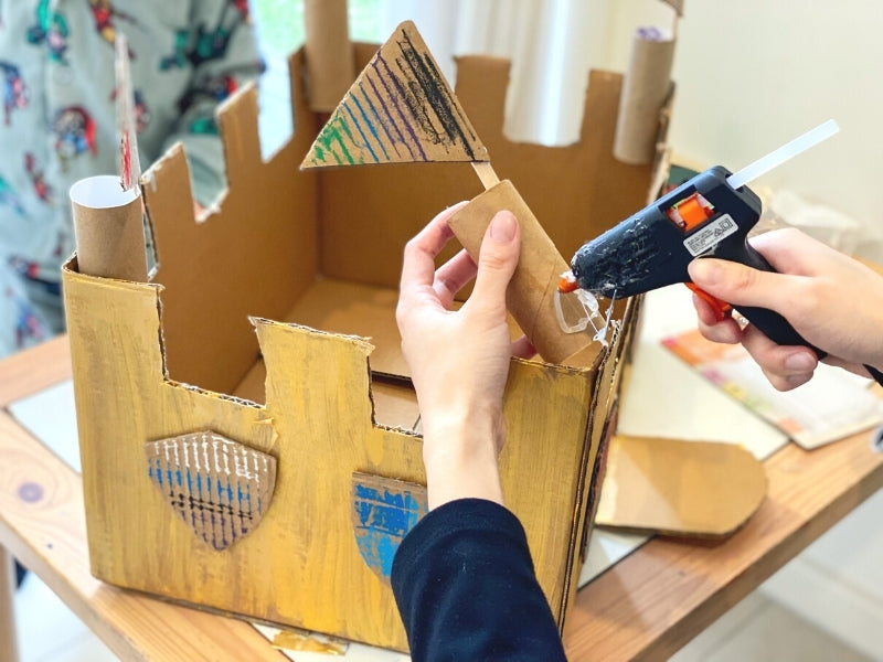 Decorate the castle walls with shields and glue on the towers with the flags.