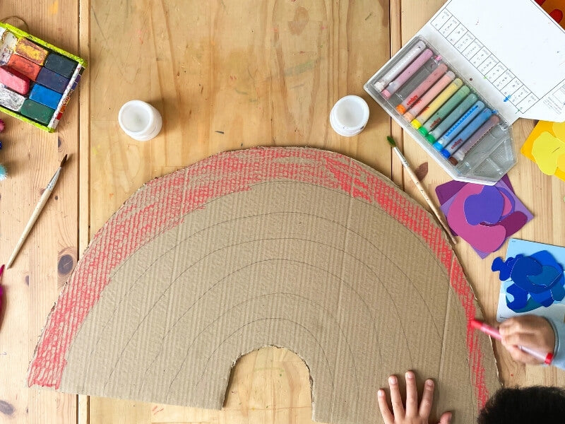Cut out a large rainbow shape from your piece of recycled cardboard