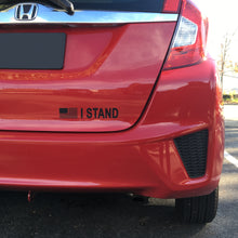 "Black ""I STAND"" decal in red background."