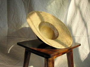 A broad brimmed straw sun hat on a wooden stool in the sunlight against a canvas backdrop.