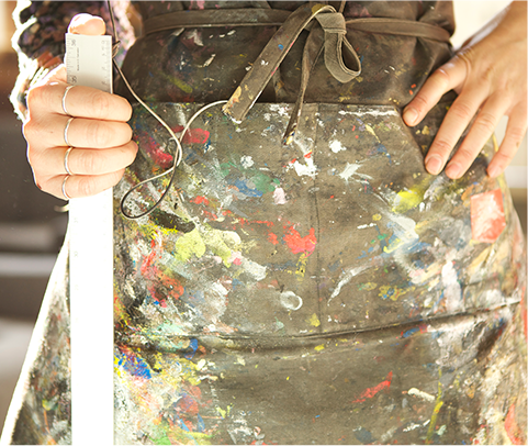 Close up of a person with an apron with paint splattered on it