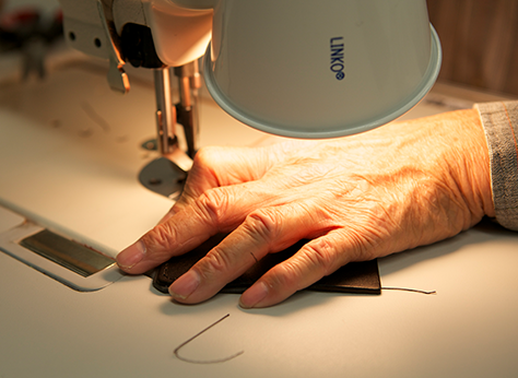 Close up of a person using a sewing machine