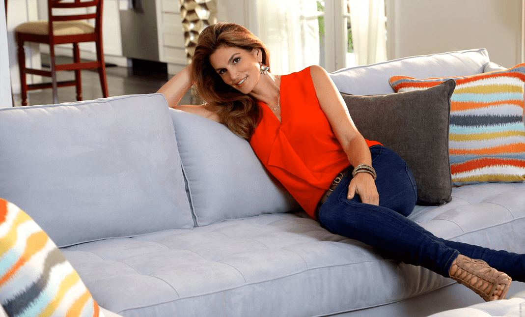 Cindy Crawford sitting on Cindy Crawford Home sofa