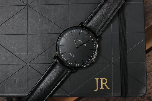 Black on Black watch on top of black notebook