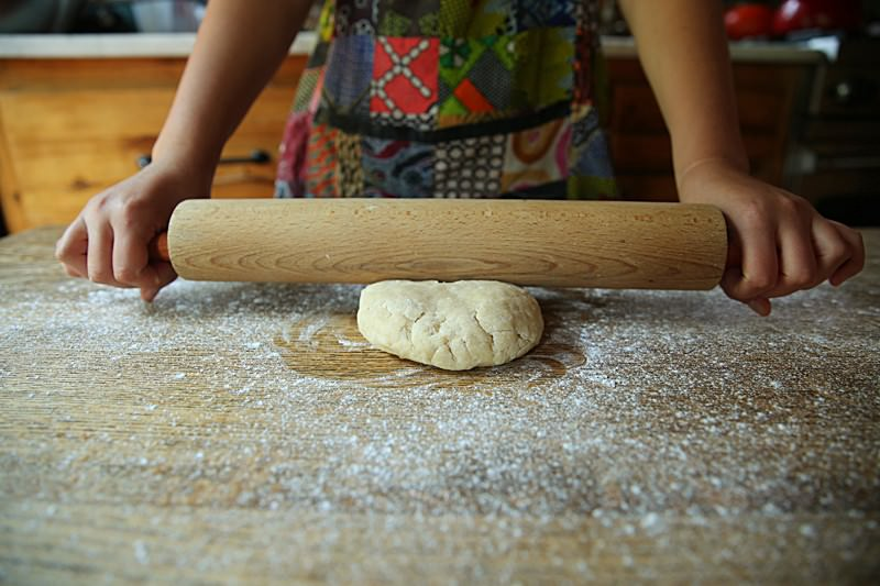 As you hold the rolling pin gently hit the surface of the dough a few times