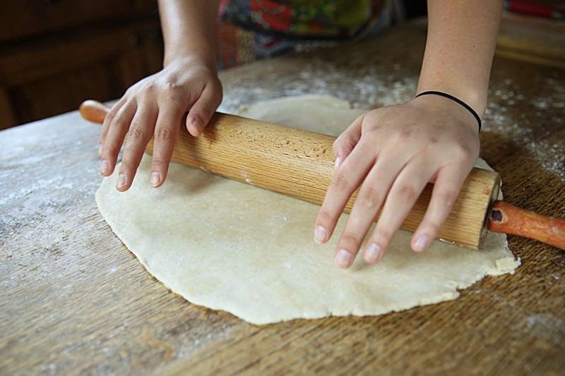 From the center, start rolling out the dough being careful to always keep the surface of the table