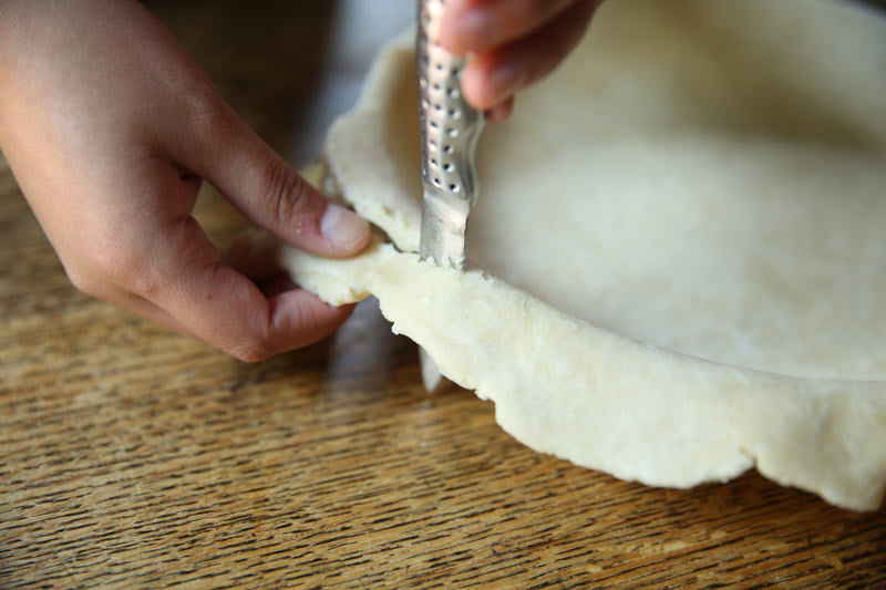 Cut the excess dough which they later used for garnish on top of the pie