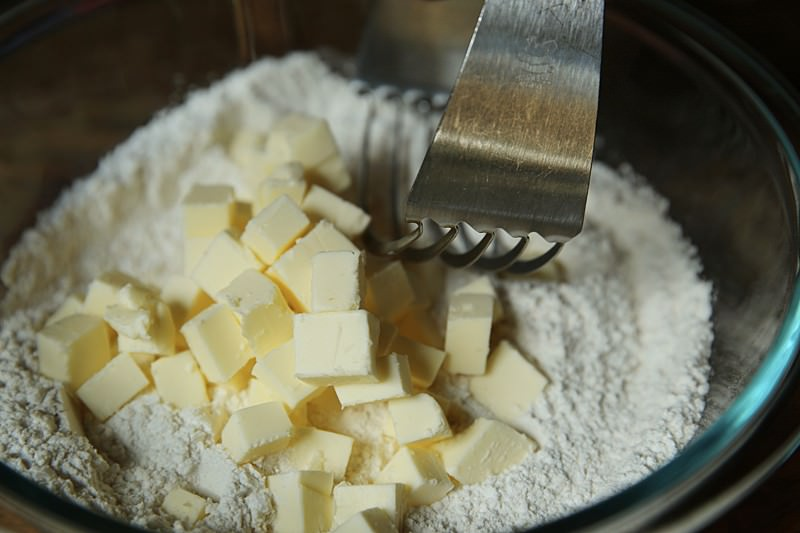 With a fork or a pastry cutter, cut the butter into the flour