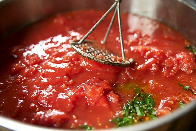 With a food masher crush the tomatoes into a thick, uniform sauce.