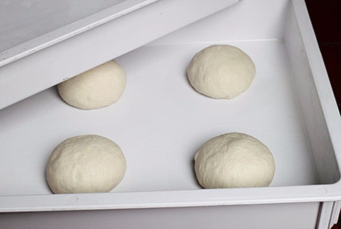 over them with either a cloth, plastic wrap or place them into stackable dough boxes