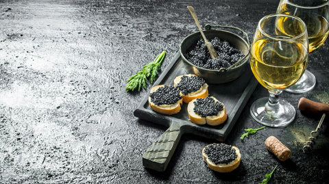 caviar in a bowl and white wine. On black rustic background