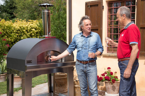 people talking in front of a outdoor pizza oven