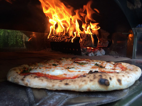 Pizza baking in fire oven
