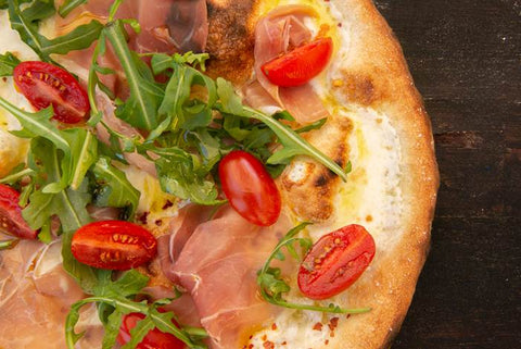 pizza with tomatoes and arugula
