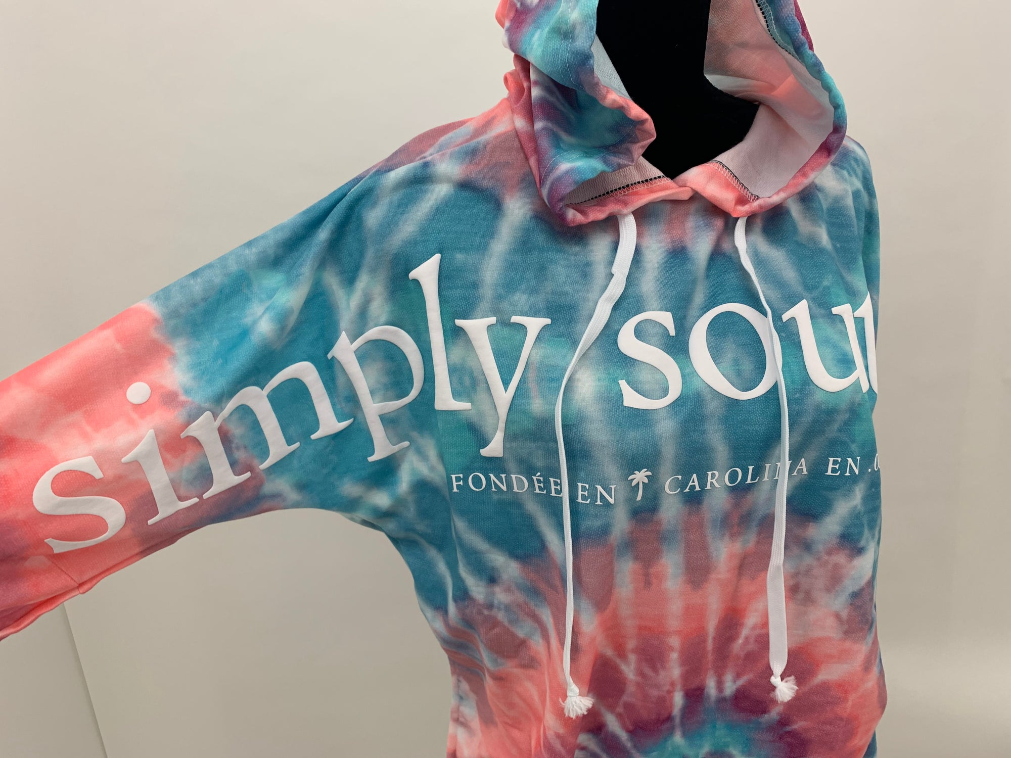 "Front picture of the Coastal swirl tie-dye hoodie sweatshirt. Comes in blue/pink/purple tie-dye, with drawstring hood, ""see the good"" label, and the Simply Southern logo across the chest. On white backdrop."