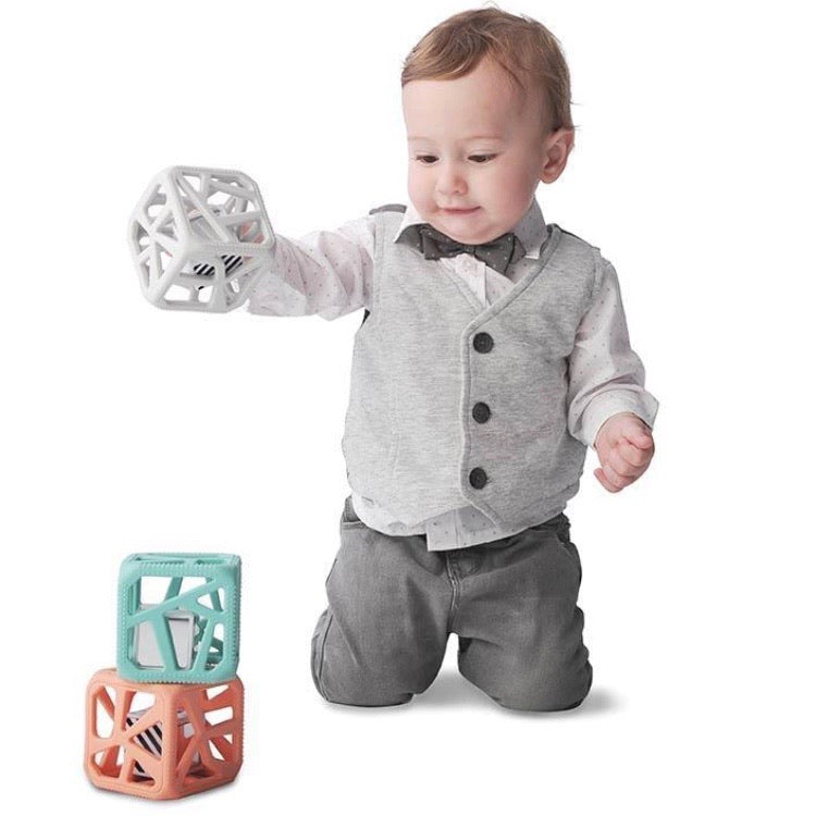 a baby sitting up on his knees stacking 3 chew cubes