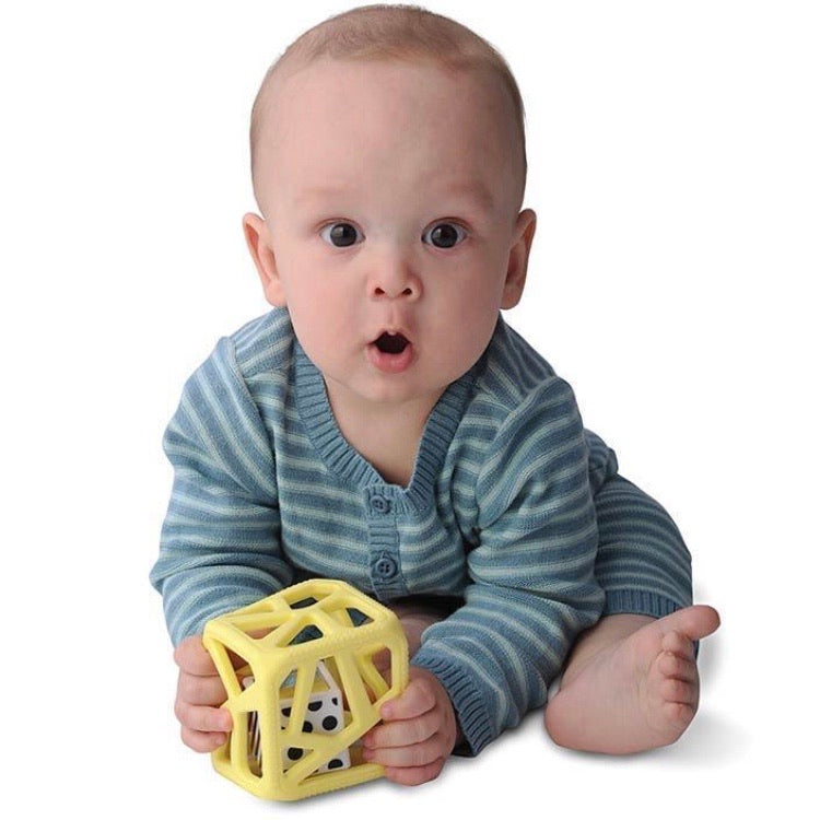 a sitting baby holding onto a chew cube in his hands