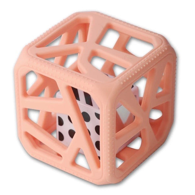 peach colored squishy silicone cube shaped baby toy with cut outs on all sides with a smaller square black & white plastic cube inside of it is shown against a white backdrop