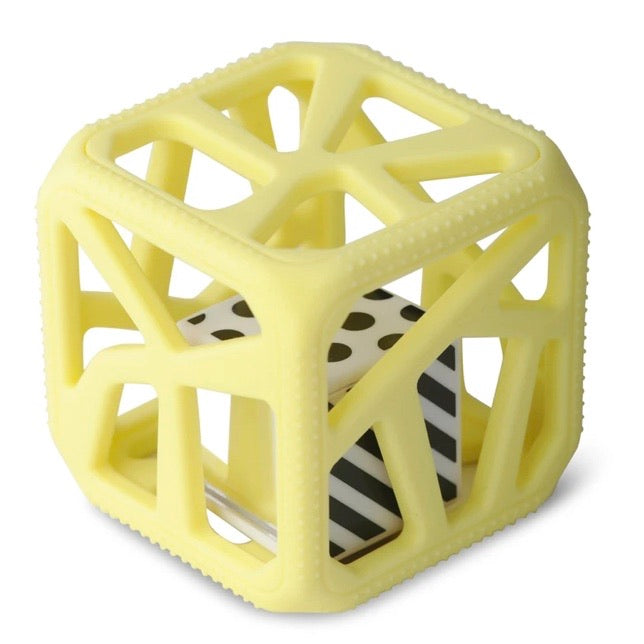 yellow colored squishy silicone cube shaped baby toy with cut outs on all sides with a smaller square black & white plastic cube inside of it is shown against a white backdrop