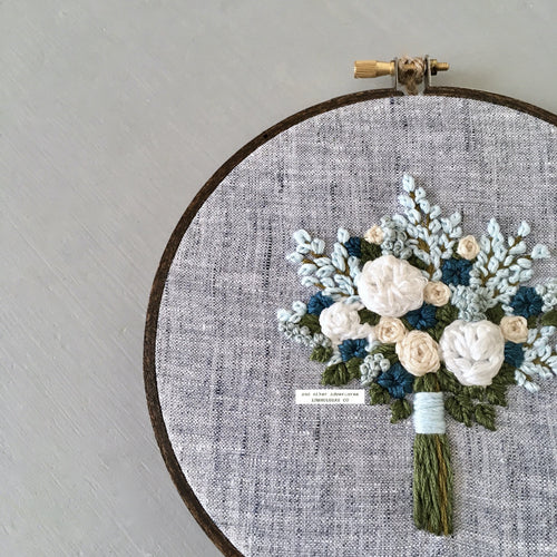 Hand Embroidered Blue Green and White bouquet hand stitched on to blue linen by And Other Adventures Embroidery Co