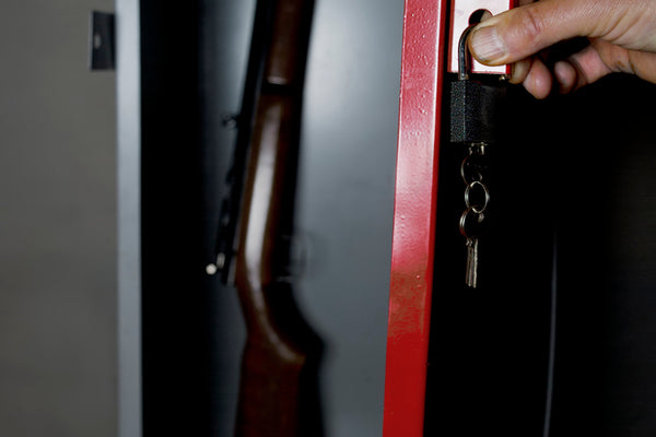 Human hand opening a childproof gun safe with a rifle inside