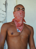 Man with an orange and red bandana tied around his face.