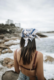 Women standing with her back turned at the beach wearing a handmade fair trade bandana on her head.