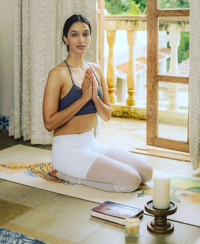 Girl meditating on an eco friendly yoga mat with incense
