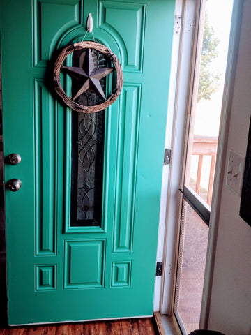 turquoise front door with rustic wooden star hanging on it