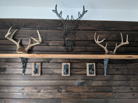 mud room dark stained ship lap wall with decorative deer horns and hooks