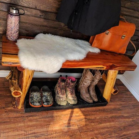 Boots under bench inside a neat rustic mud room