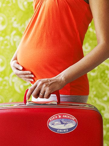 pregnant woman holding suitcase