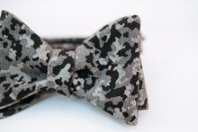 "A camouflage cotton bow tie with hues of black and variations of light and dark greys on this Japanese lightweight cotton bow tie.  Made In Japan. 100% Cotton  Height: 3"" x Width: 4.25"" x Knot Size: .75 (Approx.)  Dry Clean Only"