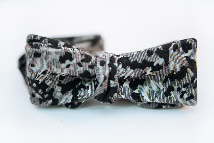 "A camouflage cotton bow tie with hues of black and variations of light and dark greys on this Japanese lightweight cotton bow tie.  Made In Japan. 100% Cotton  Height: 3"" x Width: 4.5"