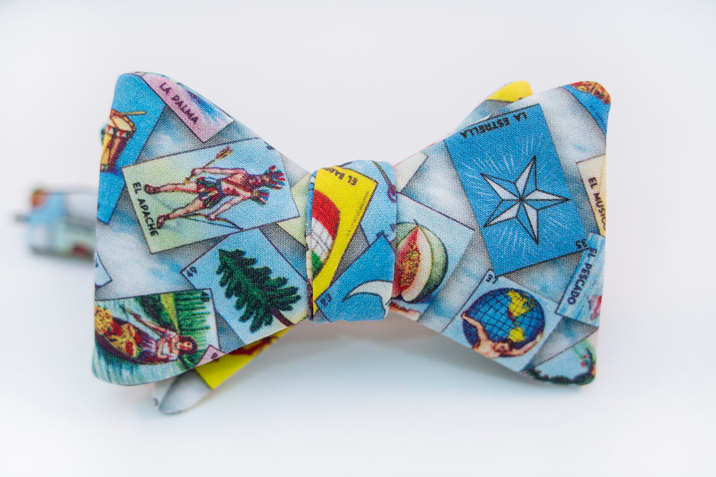 Loteria themed bow tie with dozens of possibilities of what you might get when you place your order. A lightweight cotton bow tie hoast the Loteria board game with blue/white hues as its background.   No Loteria pattern placement is guaranteed as each bow tie will vary slightly.   Height: 3